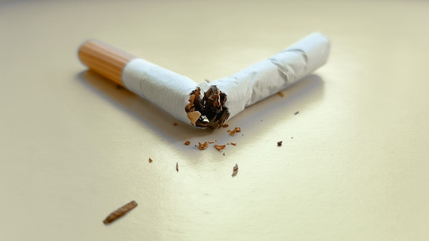 Broken cigarette isolated on a yellow background. view from above.