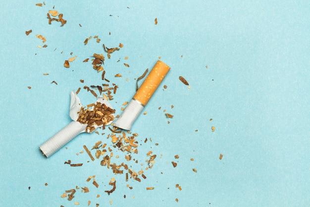 A broken cigarette on a light blue background