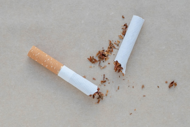 Broken cigarette on a neutral background.
