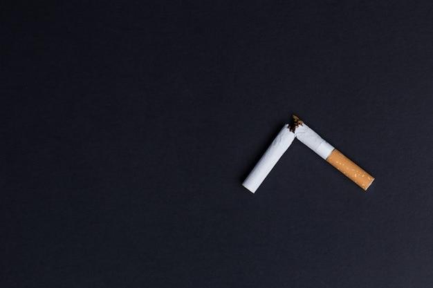 黒の背景のクローズアップに壊れたタバコ