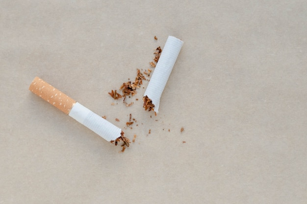 A broken cigarette on a paper background. scattered tobacco.