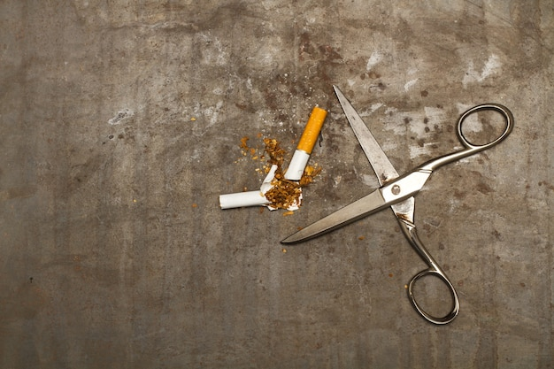 A broken cigarette and scissors on a rusty metal background