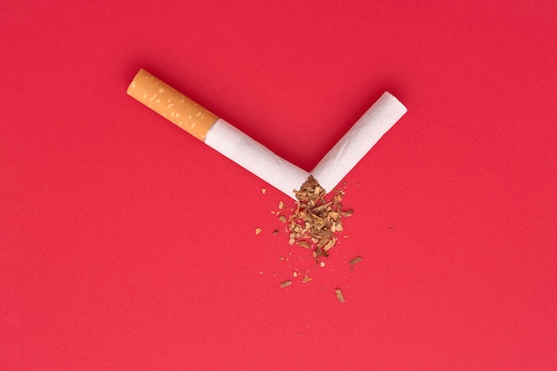 A broken cigarette with scattered tobacco on red background