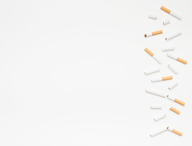 Broken cigarettes arranged on bottom over isolated on white background