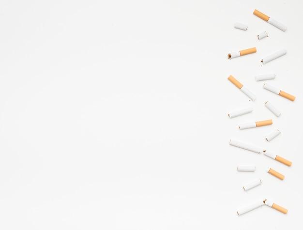 Сломанные сигареты на дне на белом фоне