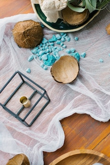 Разбитые кокосовые и синие морские декоративные камни в декоре стола. тема морского или тропического отдыха