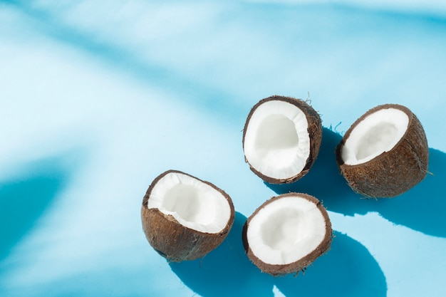 Broken coconut on a blue surface under natural light with shadows. hard light. concept of diet, healthy eating, rest in the tropics, vacation and travel, vitamins.