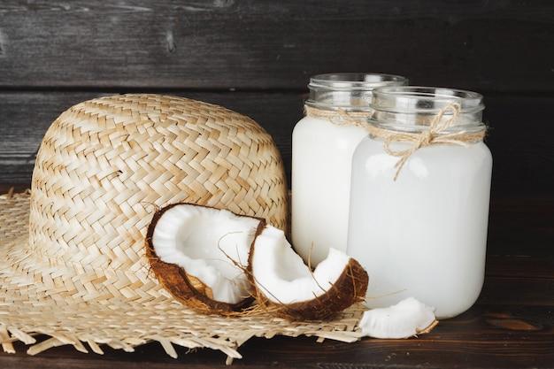 Broken coconut and coconut milk on black wooden background