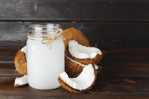 Broken coconut and coconut milk on black wooden surface