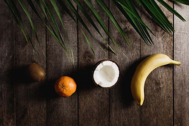 Broken coconut, kiwi, tangerine, orange, banana on brown wooden background with palm leaf. white coconut pulp. high quality photo
