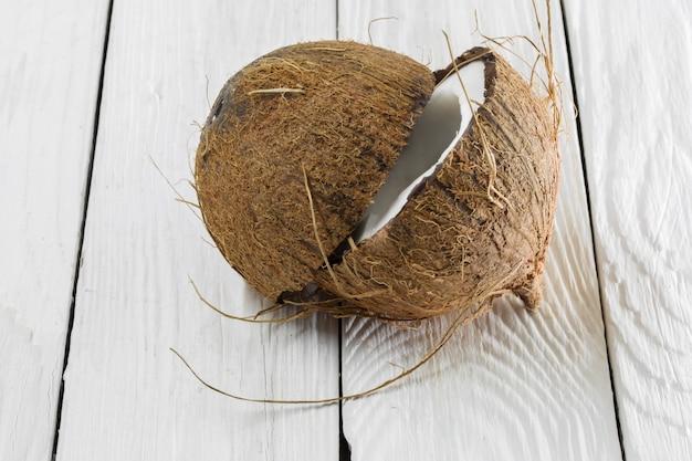 Сломанный кокос, белый деревянный фон