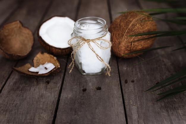 Сломанные кокосы на сером деревянном столе с флягой сырого органического кокосового масла первого отжима и пальмового листа. мякоть кокоса белая.