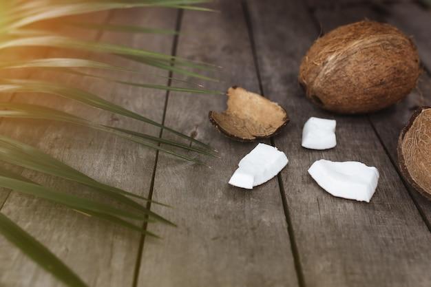 Сломанные кокосы на сером деревянном столе с пальмовым листом. мякоть кокоса белая.