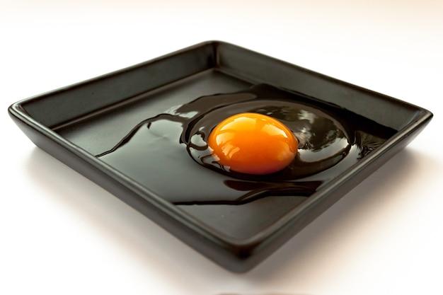 壊れたひびの入った生の新鮮な砕いた黄色の卵白と白の黒いプレート上の卵黄をクローズアップで反射します。選択的なソフトフォーカス。 。テキストコピースペース。