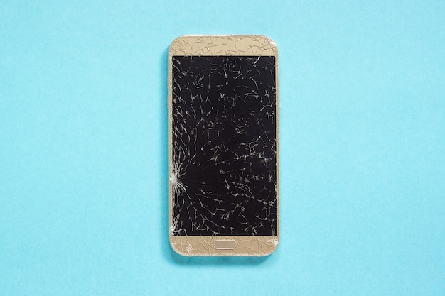Broken cracks cell mobile phone on blue background