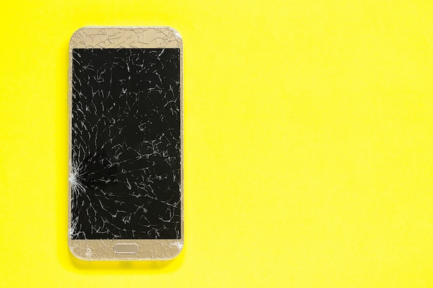 Broken cracks cell mobile phone on yellow background