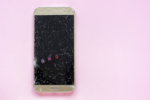 Broken cracks mobile phone and text omg on pink background