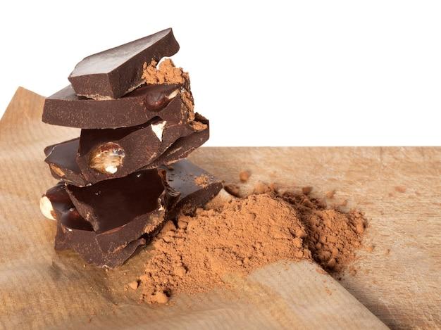 ベージュの紙の表面にアーモンドとココアパウダーが入った壊れたダークチョコレートバー。コピースペースのクローズアップショット