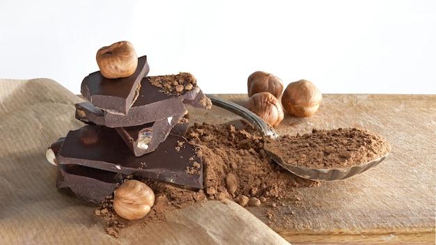 베이지 색 종이 표면에 깨진 다크 초콜릿 바, 코코아 가루 및 헤이즐넛. 클로즈업 샷