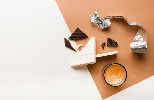 Broken dark and white chocolate bars with coffee glass on background