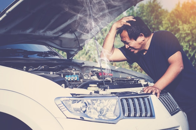 A broken down car, engine open and smoking