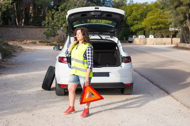 Broken down car with warning triangle. woman standing alongside her broken down car on the road and
