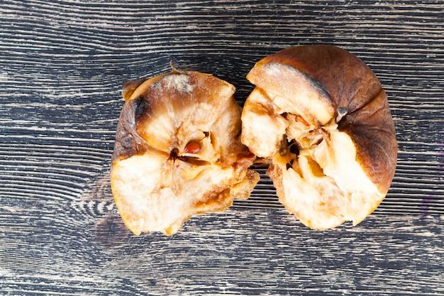 木製のテーブルの上に横たわっている半分腐ったリンゴの壊れた、クローズアップ