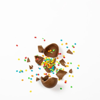 Broken easter chocolate egg and colorful decorations on a light surface. easter concept, easter treats. square. flat lay, top view
