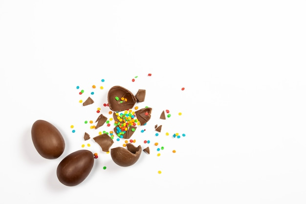 Broken easter chocolate eggs and colorful decorations on a light surface. easter concept, easter treats. flat lay, top view