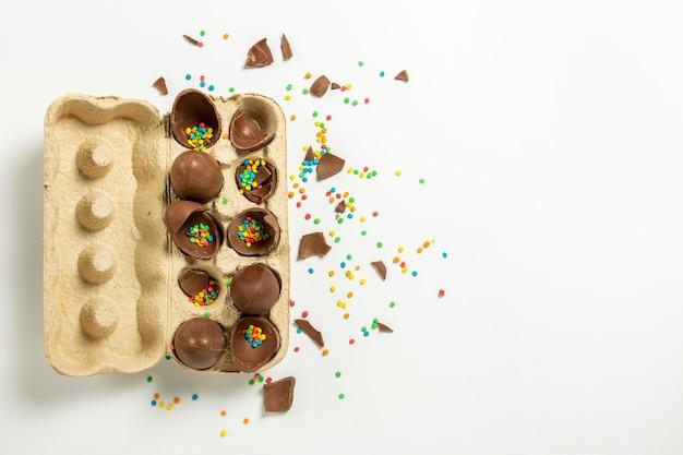 Разбитые пасхальные шоколадные яйца в подносе и разноцветные украшения на свету