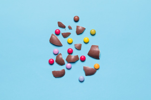 Broken easter egg shells with gem candies on blue background