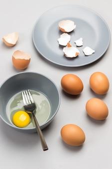 灰色のボウルと白い背景の上の灰色のプレート上の卵殻の壊れた卵とフォーク