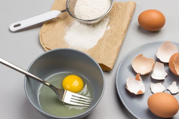 깨진 달걀과 회색 그릇에 포크. 종이에 밀가루와 체. 회색 접시에 닭 껍질입니다. 테이블에 갈색 계란. 평면도