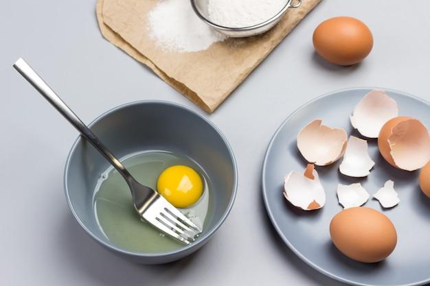 깨진 달걀과 회색 그릇에 포크. 종이에 밀가루와 체. 회색 접시에 닭 껍질입니다. 테이블에 두 개의 갈색 달걀입니다. 평면도