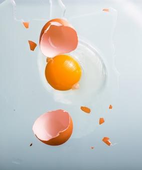 壊れた卵。卵の白と青の背景に卵黄。閉じる