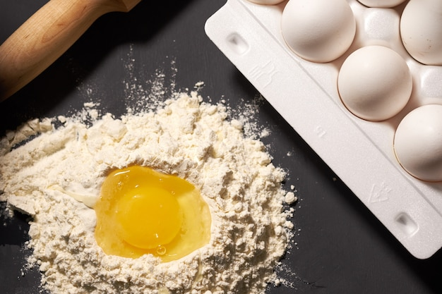 Broken egg in flour, next to a rolling pin and whole eggs