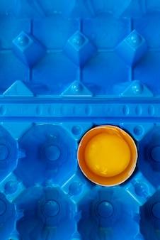 Разбитое яйцо в ярко-желтый контейнер. белый абстрактный фон. яичная скорлупа и желток