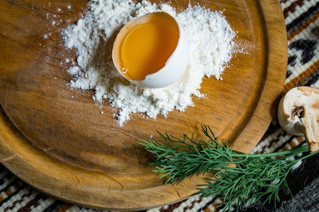 냅킨을 가진 어두운 나무 테이블에 둥근 커팅 보드에 밀가루에 깨진 달걀