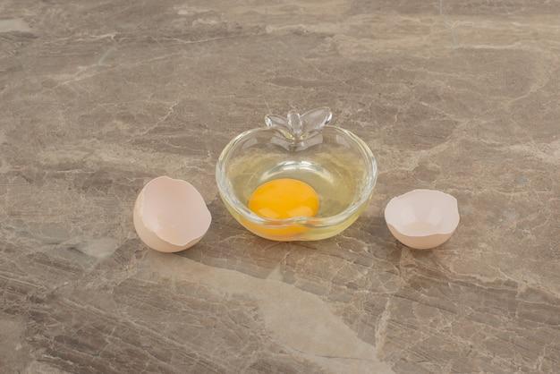 大理石のテーブルのプレート上の壊れた卵。