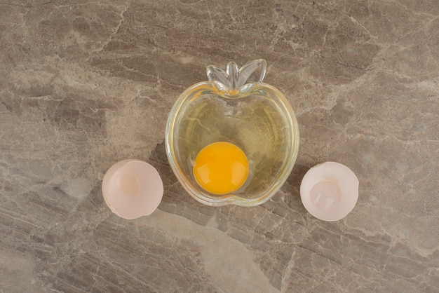 Broken egg on plate on marble table .