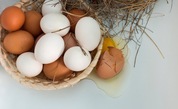 Broken egg with a wicker wooden plate with eggs on a white background, top view.