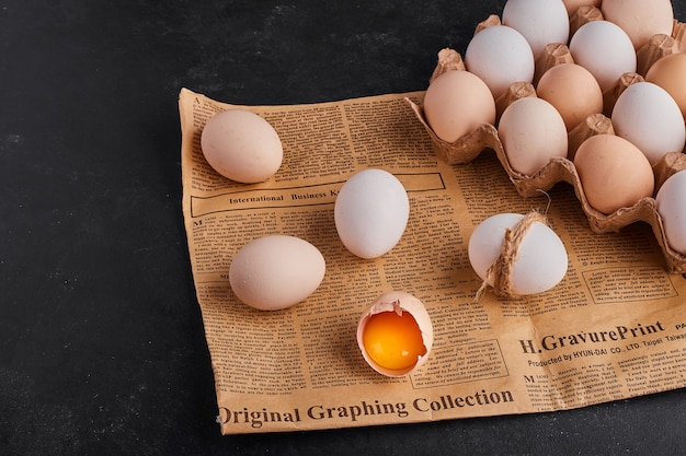 Broken eggs on a piece of newspaper and on cardboard container.