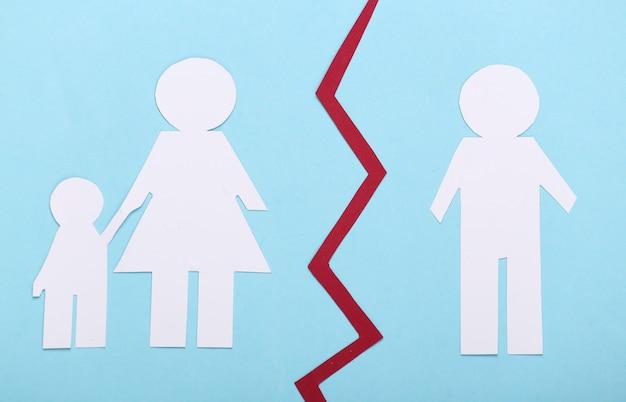 Broken family, divorce. deprivation of parental rights. split paper family on blue