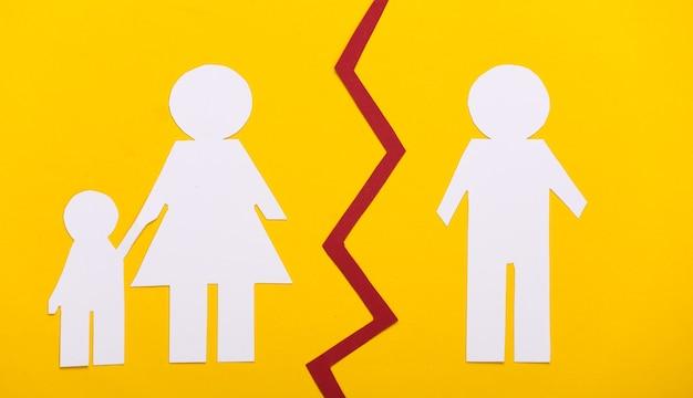 Broken family, divorce. deprivation of parental rights. split paper family on yellow