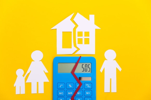 Broken family, divorce. property division concept. split paper family, calculator  and house on yellow