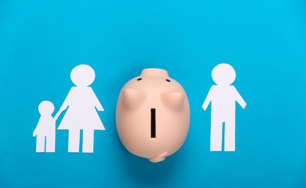 Broken family, divorce. property division concept. split paper family, piggy bank on blue