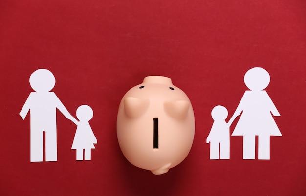 Broken family, divorce. property division concept. split paper family, piggy bank on a red