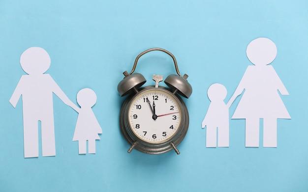 Broken family, divorce. split paper family, alarm clock on blue