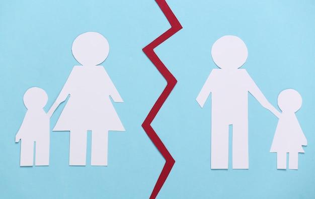 Broken family, divorce. split paper family on blue