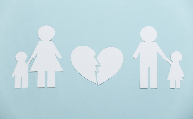 Broken family, divorce. split paper family, broken heart on blue